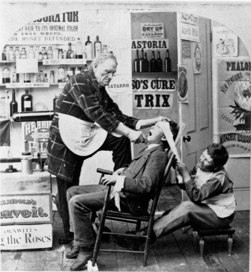 A man pulls another's tooth in a room filled with a variety of medicines. 1872.