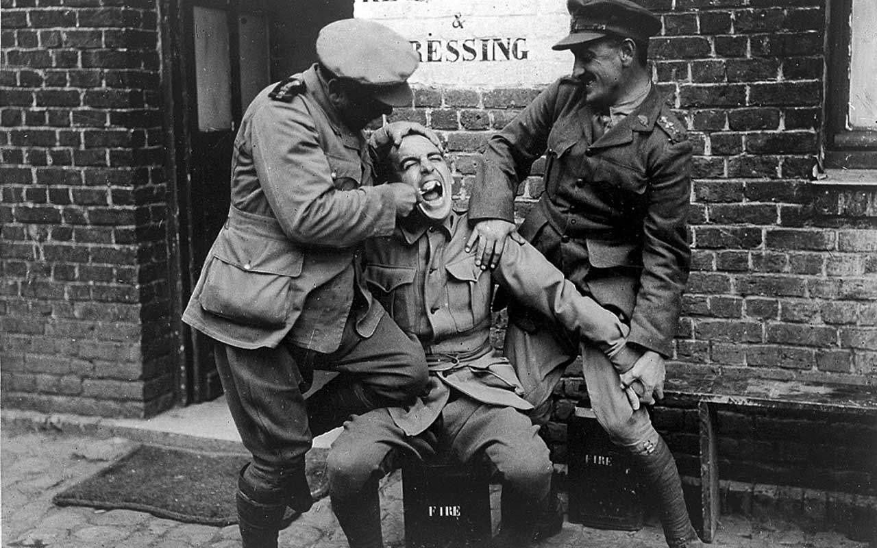 Comic photograph of Army officers cleaning their friend's teeth. Circa World War II.